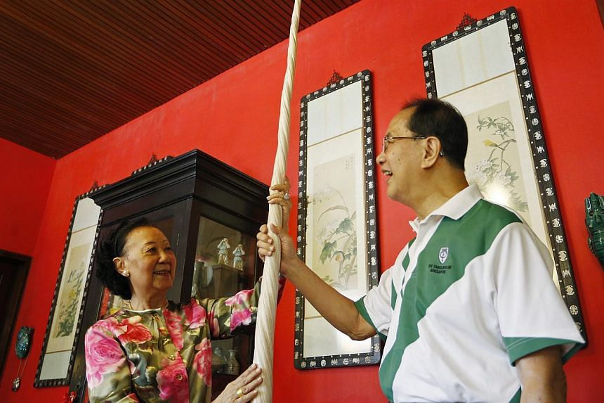 Madam Hoo Miew Oon (left) and her husband Yap Boh Lee (right) with the rare narwhal tusk that was donated to the new Lee Kong Chian Natural History Museum on Wednesday. It had belonged to her great-grandfather Whampoa Hoo Ah Kay. -- PHOTO: DESMOND LU