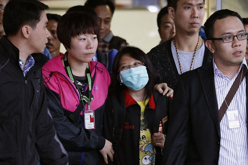 Ms Erwiana Sulistyaningsih (centre) being escorted out of the airport in Hong Kong in April, on her return to the city for a medical examination as part of the investigation into her case. -- PHOTO: REUTERS