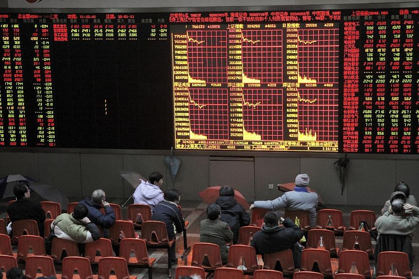 Investors watch the stock trading board at a securities exchange house in Shanghai, China. Four mainland Chinese IPOs drew huge demand after a four month hiatus on offerings. -- PHOTO: BLOOMBERG