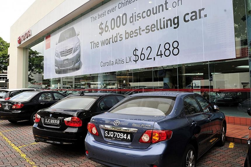 Toyota showroom at Leng Kee Complex. Car certificate of entitlement (COE) prices have tumbled by more than 20 per cent since April, but not all car prices have fallen in tandem. -- PHOTO: ST FILE