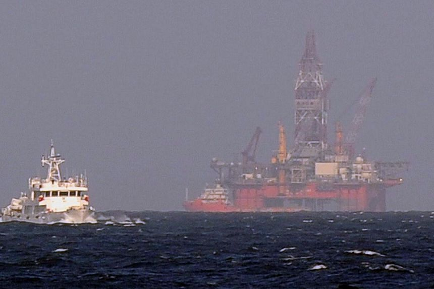 This file picture taken on May 14, 2014 from a Vietnamese coast guard ship shows a Chinese coast guard vessel (L) sailing near a Chinese oil rig in disputed waters in the South China Sea. -- PHOTO: AFP
