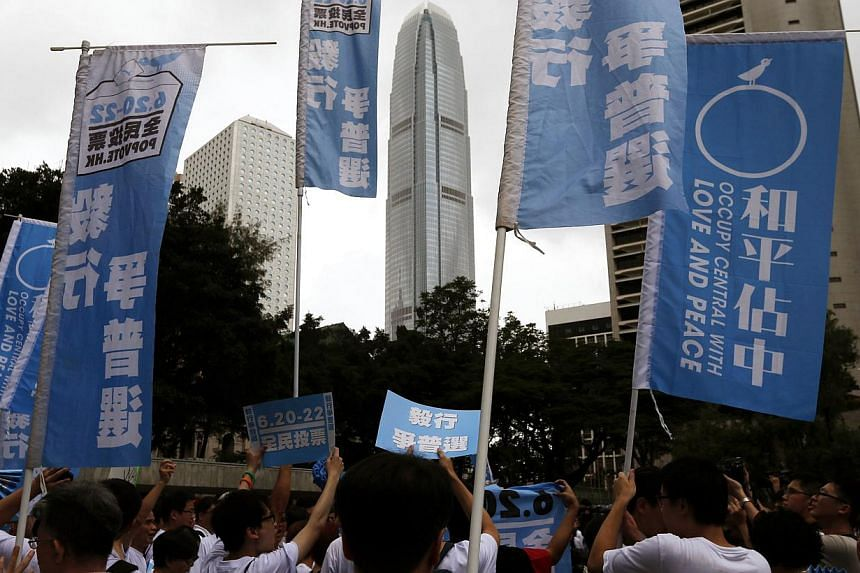 Supporters hold banners and placards at Hong Kong's financial Central district during a kick-off ceremony to urge people to vote in an unofficial referendum on June 20, 2014.More than 160,000 people took part in an unofficial Hong Kong vote on