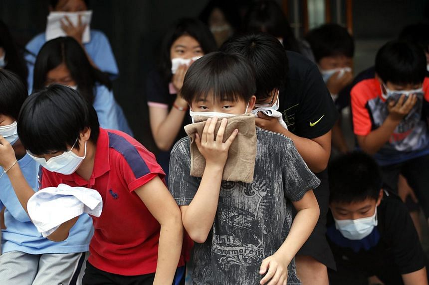 South Korean elementary school students take part in a evacuation exercise as a part of civil defence training in Seoul on June 20, 2014. -- PHOTO: REUTERS