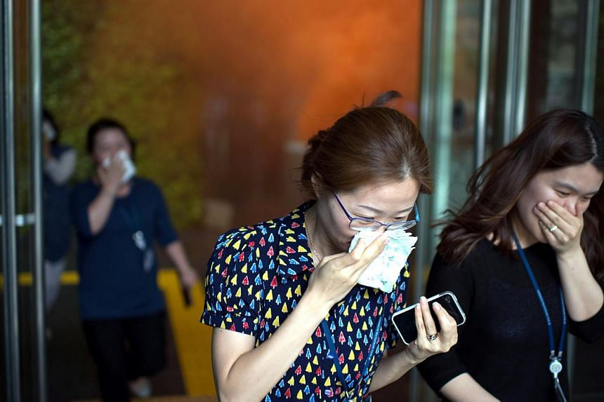Office workers evacuate Seoul City Hall during a nationwide fire drill on June 20, 2014. -- PHOTO: AFP