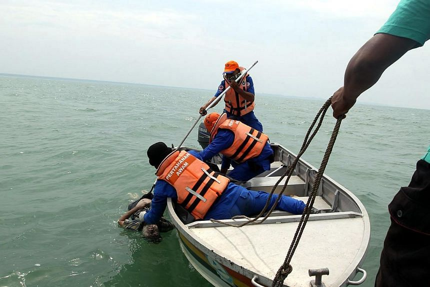 Rescuers pull bodies of victims of sunken boat at Kampung Kelamang Banting.Malaysian authorities said on Friday they have arrested two Indonesian men in connection with one of two boat accidents that have left 15 people dead and 27 others still