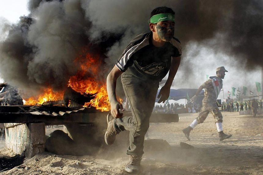 A Palestinian youth runs as he takes part in military-inspired exercises during a summer camp organised by the Islamist movement Hamas on June 19, 2014, in Rafah, southern Gaza Strip. -- PHOTO: AFP