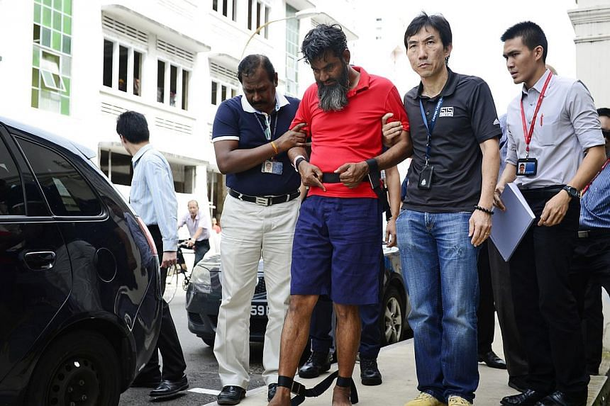 Suitcase murder Pakistani suspect, Rasheed Muhammad, 43, uses his foot and fingers to point to what appears to be dried blood stains on the pavement along Syed Alwi Road. -- PHOTO: ST FILE