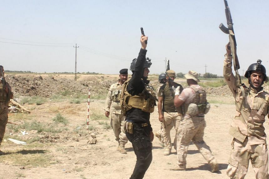 Members of the Iraqi security forces shout slogans as they carry weapons during clashes with Sunni militant group Islamic State of Iraq and the Levant (ISIL) in Muqdadiyah in Diyala province on June 19, 2014. -- PHOTO: REUTERS