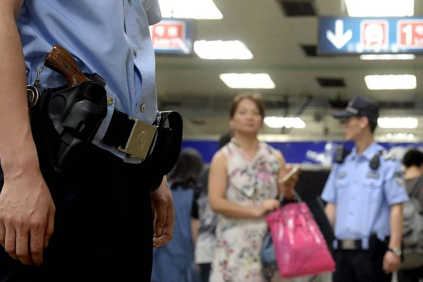 Armed policemen stand guard in a subway, after attackers ploughed two vehicles into a market and threw explosives, killing at least 31 people in Urumqi in northwest China's Xinjiang region, in Beijing on May 23, 2014. -- PHOTO: AFP