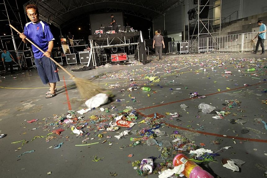 """A janitor cleaning up litter after a New Year countdown party on Jan 1, 2011.While enforcement is still important to take litterbugs to task, there is also a need to """"establish values and social norms"""" in public hygiene, said Second Minister fo"""