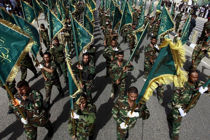 Iraqi security forces, loyal to Muslim Shi'ite cleric Moqtada al-Sadr take part in a military parade on June 21, 2014 in the shrine city of Najaf, in central Iraq.Washington readied a new diplomatic push to unite Iraq's fractious leaders on Sat
