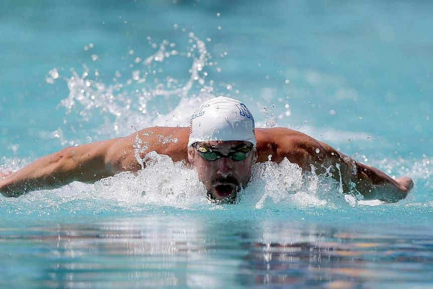 Michael Phelps competes in the men's 100m butterfly preliminaries during the 2014 Arena Grand Prix of Santa Clara at the George F. Haines International Swim Center on June 20, 2014, in Santa Clara, California.-- PHOTO: AFP