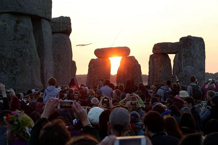 Revelers watch and take photos as the sun rises over the standing stones at the prehistoric monument Stonehenge, near Amesbury in Southern England, on June 21, 2014, as revelers gather to celebrate the 2014 summer solstice, marking the longest day of