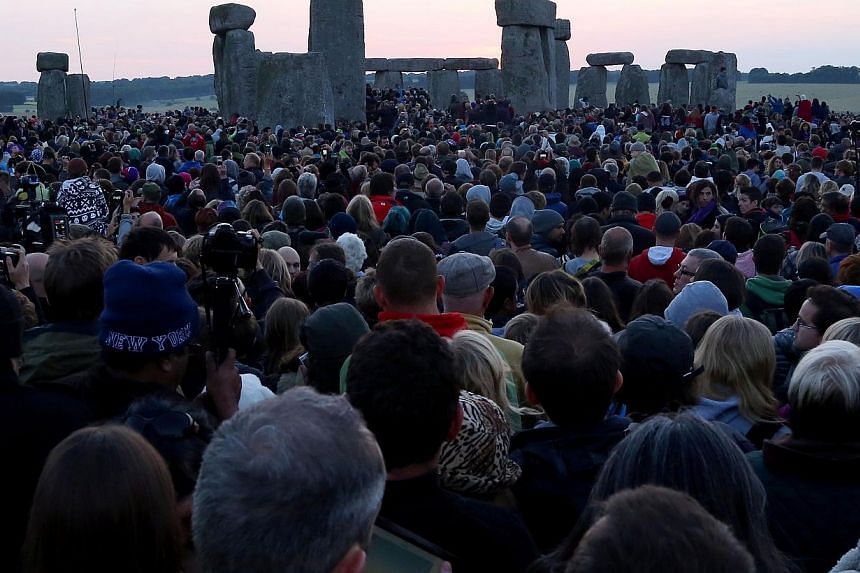 Revelers gather as the sun rises at the prehistoric monument Stonehenge, near Amesbury in Southern England, on June 21, 2014 to mark the summer solstice, the longest day of the year. -- PHOTO: AFP