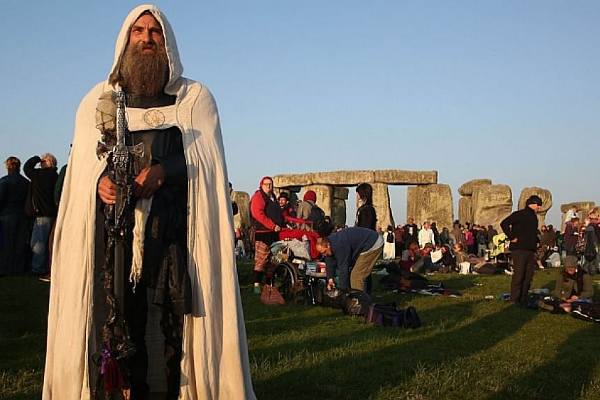 A modern druid named Merlin stands as the sun rises at the prehistoric monument Stonehenge, near Amesbury in Southern England, on June 21, 2014 as revelers gether to mark the summer solstice, the longest day of the year. -- PHOTO: AFP