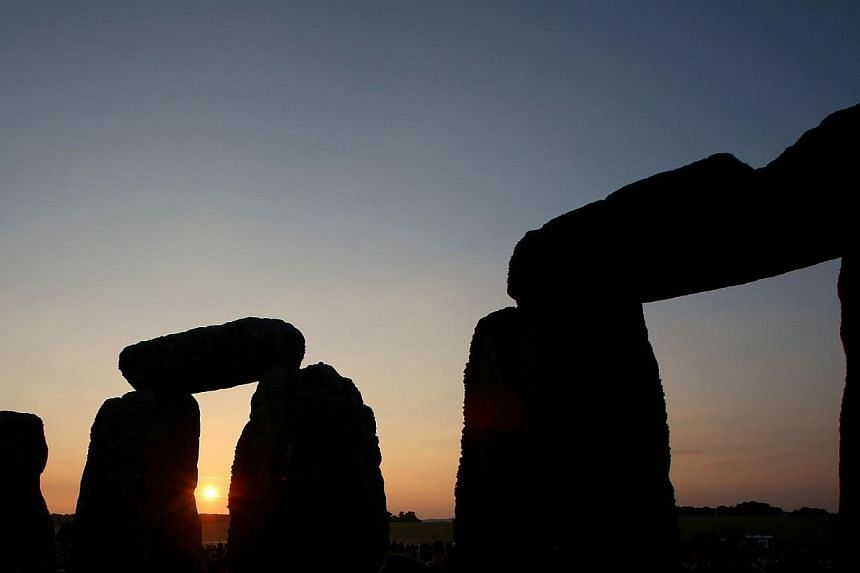 The sun rises over the standing stones at the prehistoric monument Stonehenge, near Amesbury in Southern England, on June 21, 2014, as revelers gather to celebrate the 2014 summer solstice, marking the longest day of the year. -- PHOTO: AFP