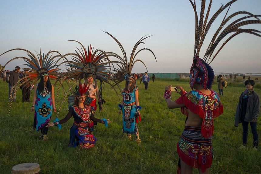 Revellers dressed in Aztec costume celebrate the summer solstice on Salisbury Plain in southern England on June 21, 2014. -- PHOTO: REUTERS