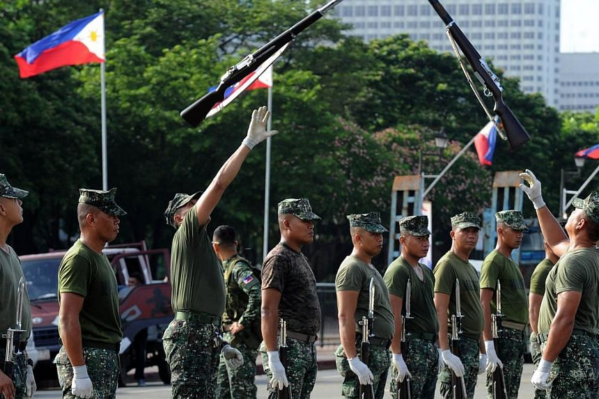 Soldiers toss their rifles into the air as members of the Philippine Army practice a ceremony on the eve of the country's Independence Day at Luneta Park in Manila on June 11, 2014. The Philippine army is getting a much-needed upgrade with the arriva