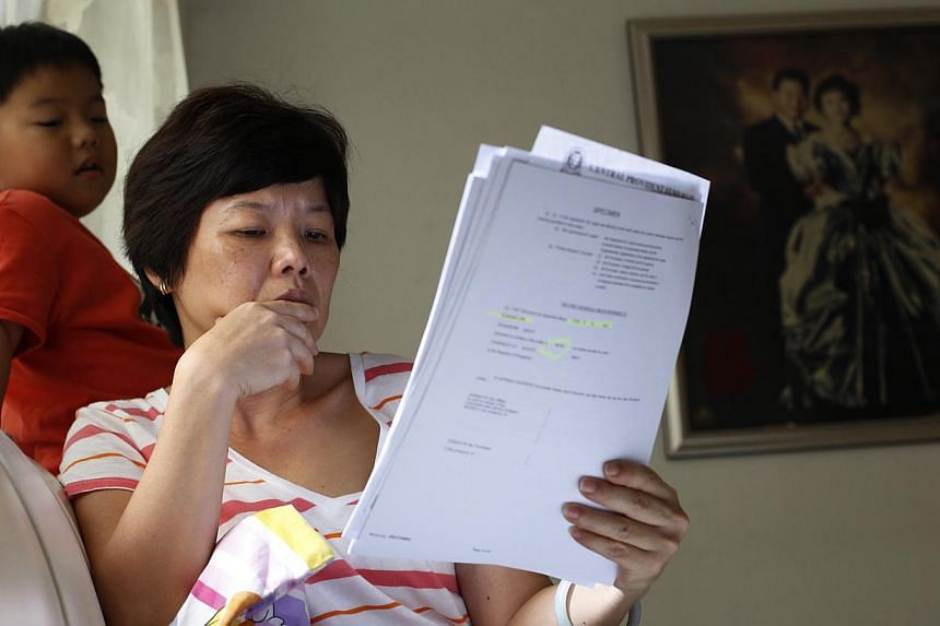 Housewife Niki Liu reading letters from the CPF Board and HDB as her youngest child Rey Phua looks on. She has been thinking twice about maintaining her IP in the face of rising premiums.