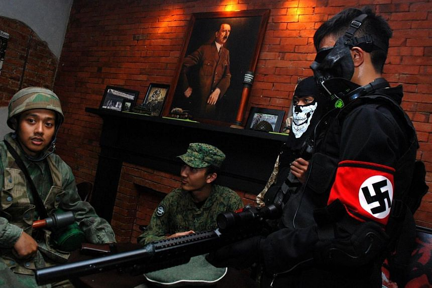 Indonesian customers coming in World War II motif military uniforms, one bearing a Nazi's swastika insignia while a portrait of Adolf Hitler hangs in the background, at the reopened SoldatenKaffee in Bandung city, western Java island on June 21, 2014