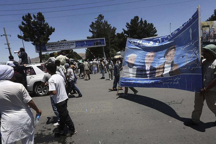 Afghan protesters carry a poster of presidential candidate Abdullah Abdullah during a demonstration in Kabul on June 21, 2014. Protesters gathered in the Afghan capital on Saturday in support of presidential candidate Abdullah Abdullah's accusation o