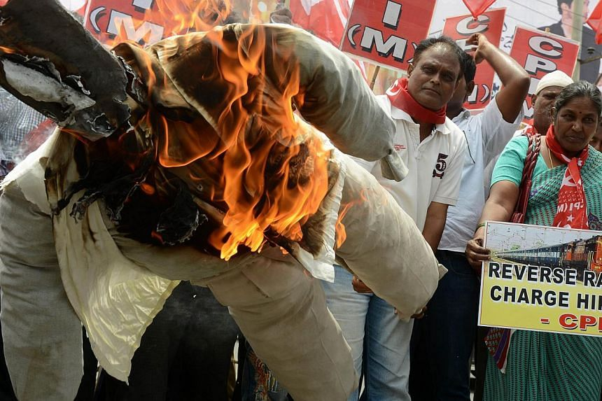 Indian activists of the Communist Party of India-Marxists (CPI-M) burning an effigy representing Prime Minister Narendra Modi during their protest against the price hike in railway fares, in Hyderabad on June 21, 2014. The government has increased th