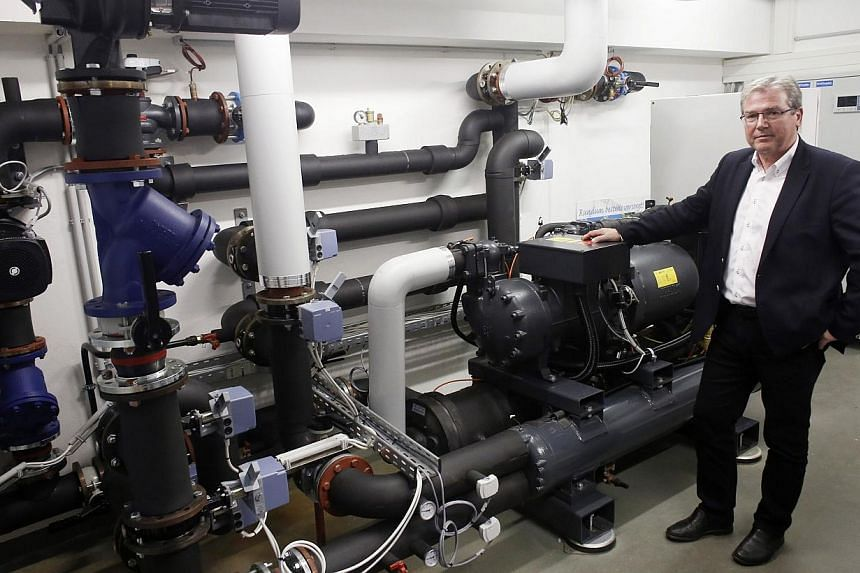 The director of the municipal services of Amstetten Robert Simmer is pictured in front of a heat pump on May 7, 2014 in Amstetten, Austria. A pilot project in the town of Amstetten by a local utility company is recycling heat energy from the sewer, h