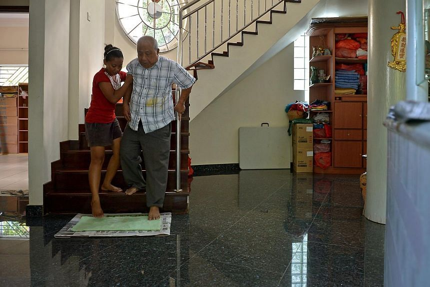 ONE MAID NOT ENOUGH:Indonesian maid Siti (left), who goes by one name, cleaning the house porch with her employer Liew Bee Choo, and helping Mr Liew (above) down the stairs. The Liews' second maid is arriving this week.