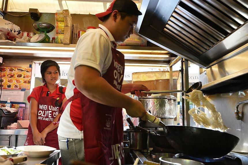 ITE student Sebastian Chua, 17, cooking sum lo hor fun at Hong Kong Street Old Chun Kee in Makansutra Gluttons Bay as his course mate Ilyzyana Kamis looks on. -- ST PHOTO: MARK CHEONG