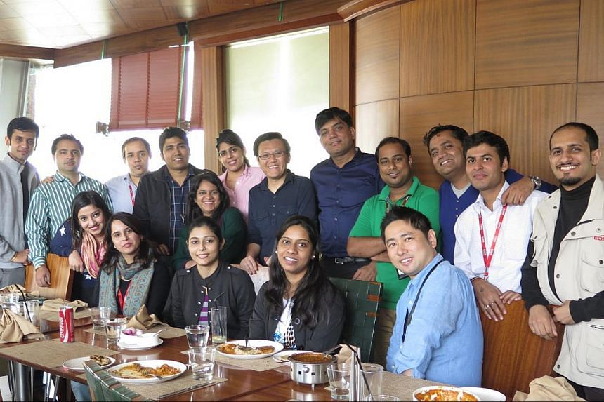 Mr Koh (standing, centre) with his colleagues at a team lunch. Last August, Canon India appointed him to oversee the brand's camera business. Below is a photograph of him taken 20 years ago when he was a manager in a local firm. -- PHOTO: COURTESY