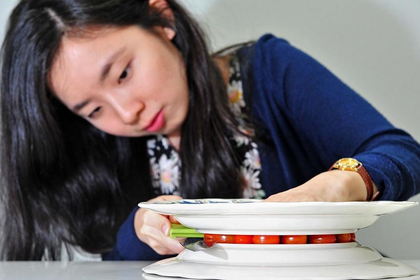 KITCHEN TECHNIQUES: Digital marketer Lisa Tan (above), learnt how to slice tomatoes evenly by placing them between two plates before wielding a knife. -- PHOTO: STEFFI KOH