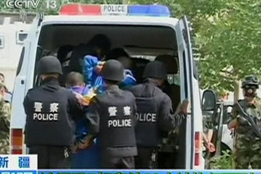 Riot policemen lead men who are about to be executed into a police van in this still image taken from video in an unknown location in the Xinjiang Uighur Autonomous Region, June 16, 2014. -- PHOTO: REUTERS