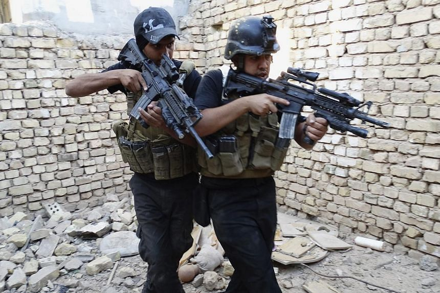 Members of the Iraqi Special Operations Forces take their positions during a patrol looking for militants of the Islamic State of Iraq and the Levant (ISIL), explosives and weapons in a neighbourhood in Ramadi, on June 11, 2014. Escalating viole