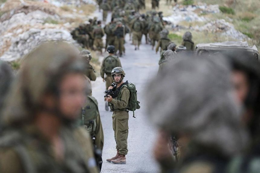 Israeli soldiers take part in an operation to locate three Israeli teens near the West Bank City of Hebron on June 21, 2014. -- PHOTO: REUTERS