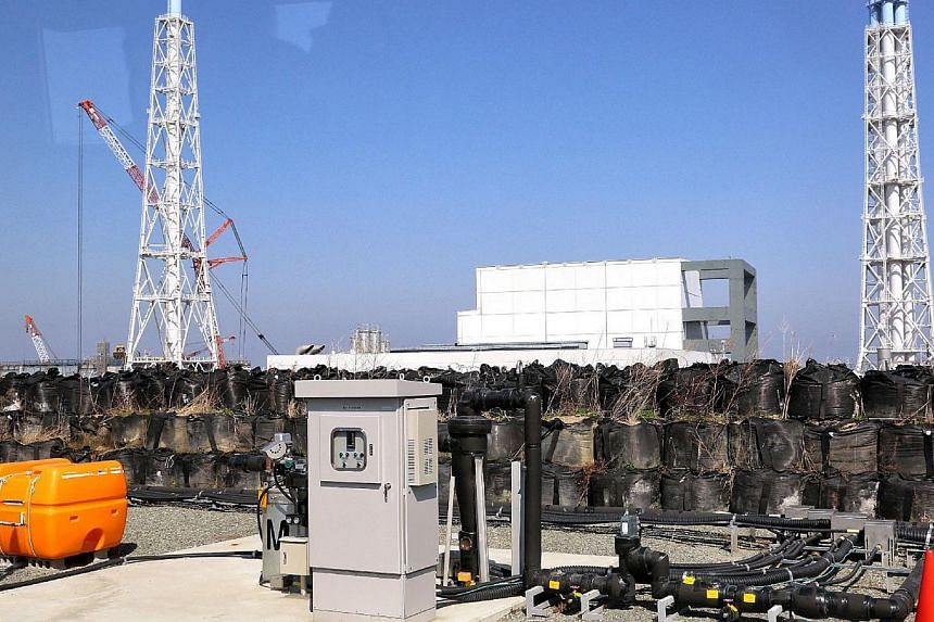 This picture taken on April 15, 2014, shows a facility to pump up underground water at the Tokyo Electric Power CO (Tepco) Fukushima Dai-ichi nuclear power plant at Okuma town in Fukushima prefecture, with the unit 3 and 4 reactor buildings behind.&n
