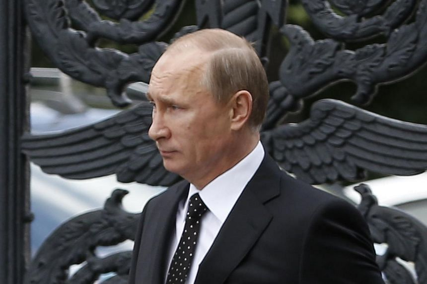 Russia's President Vladimir Putin walks to attend a ceremony to commemorate the anniversary of the beginning of the Great Patriotic War against Nazi Germany in 1941 near memorials by the Kremlin walls in Moscow on June 22, 2014.Russian Presiden