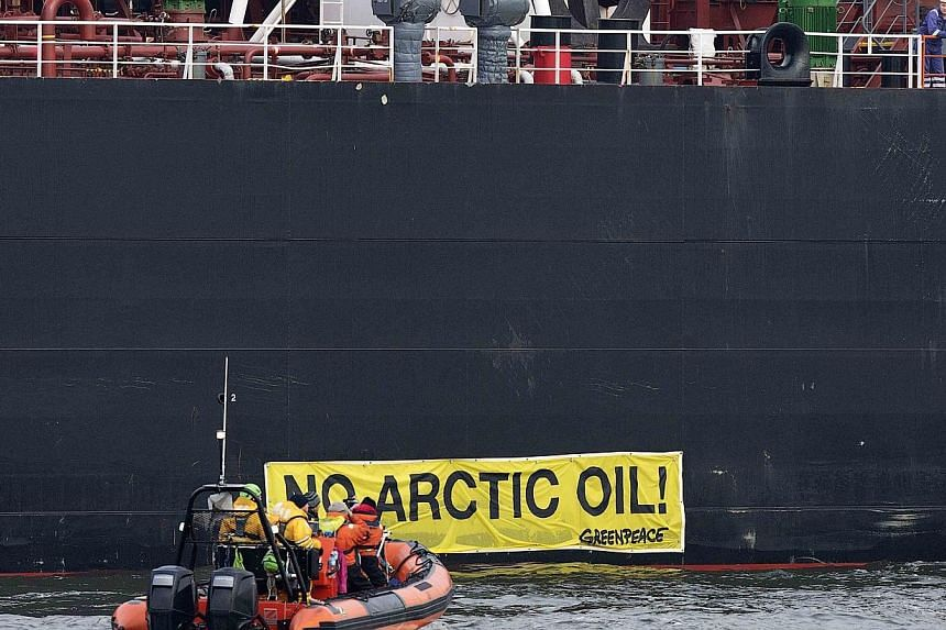 """A crew member of the Russian oil tanker Mikhail Ulyanov looks on as members of Greenpeace sail past a banner saying """"No Arctic Oil"""" on the vessel in the harbour of Rotterdam on May 1, 2014.Tens of degrees below zero during winter and home to en"""