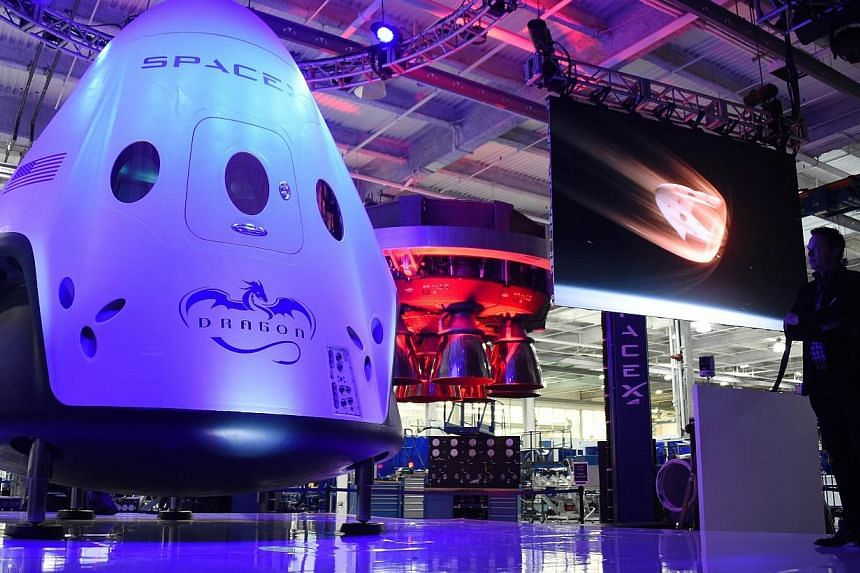 SpaceX CEO Elon Musk (right) unveils SpaceX's new seven-seat Dragon V2 spacecraft, at a press conference in Hawthorne, California, on May 29, 2014. Space Exploration Technologies, or SpaceX, on Saturday delayed the planned launch of a Falcon 9 r