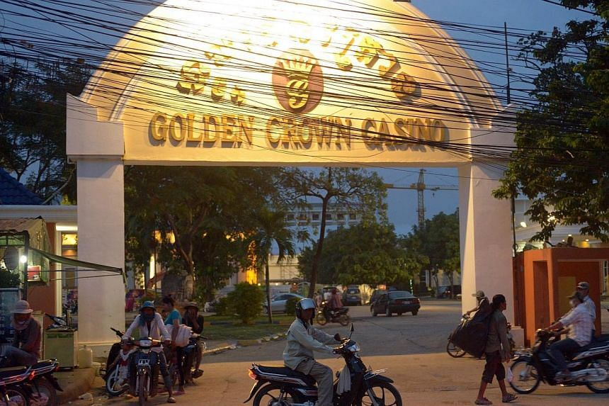 In a picture taken on June 19, 2014, a Cambodian man rides his motorbike past a gate of the Golden Crown Casino in the Thai-Cambodian border city of Poipet, northeastern Cambodian province of Banteay Meanchey. -- PHOTO: AFP