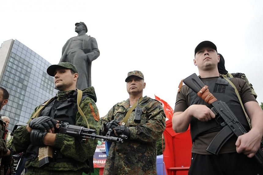 Pro-Russian militants take the military oath of allegiance to the so-called People's Republik of Donetsk during the ceremony in the eastern Ukrainian city of Donetsk on June 21, 2014.Ukraine's unilateral ceasefire hung in the balance on Satur