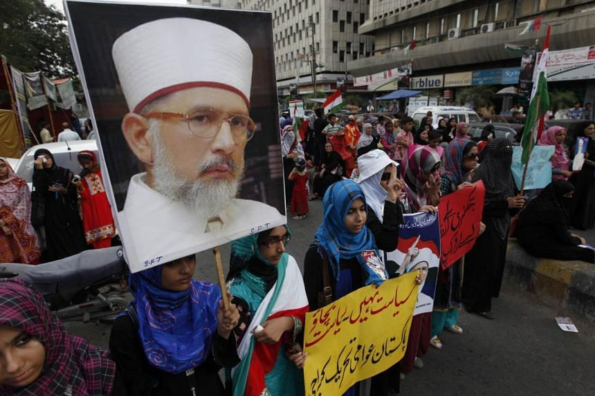 Female supporters of Tahir-ul Qadri carrying his portrait during a protest last week in Karachi. The prominent cleric had been expected to arrive in Islamabad yesterday to lead what he describes as a revolution against Pakistan Prime Minister Nawaz S