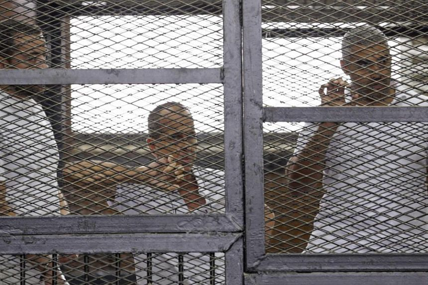 Al-Jazeera journalists (from left) Baher Mohamed, Peter Greste and Mohammed Fahmy behind bars in a court in Cairo earlier this month. The three were accused of aiding the blacklisted Muslim Brotherhood. PHOTO: REUTERS