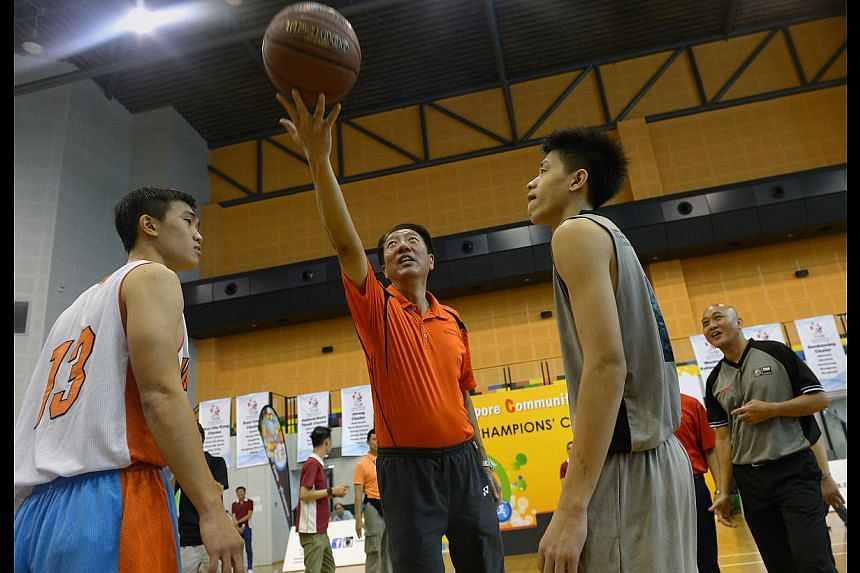 DPM Teo Chee Hean tossing the ball for the basketball final between Nee Soon South Constituency Sports Club (in grey) and Jalan Kayu Community Sports Club. The latter won the game 61-42.