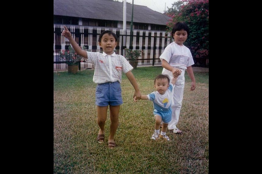 Ethan Koh as a toddler (above left) wearing his now-signature bow-tie in front of colourful plants, a source of inspiration for his creations today, and in the backyard of his childhood home (above) in Kovan Road with his older brother Albert and sis