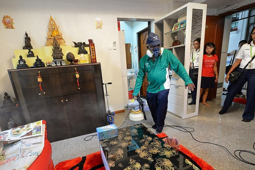 An environmental support assistant from the NEA spraying the living room of a private house along Simon Lane, in the Kovan area, with ultra-low-volume cold misting to fight dengue. The Government is paying particular attention to the area spanning Se