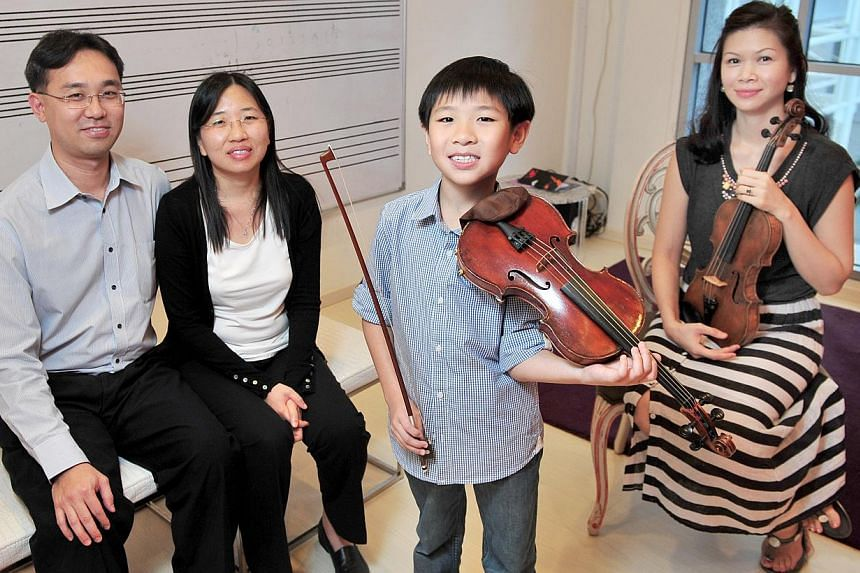 Young violinist Samuel Tan enjoys going for competitions because they offer him a chance to see other people playing the instrument. With him are his parents Jason Tan and Janis Low (both left) and his teacher Lee Huei Min.