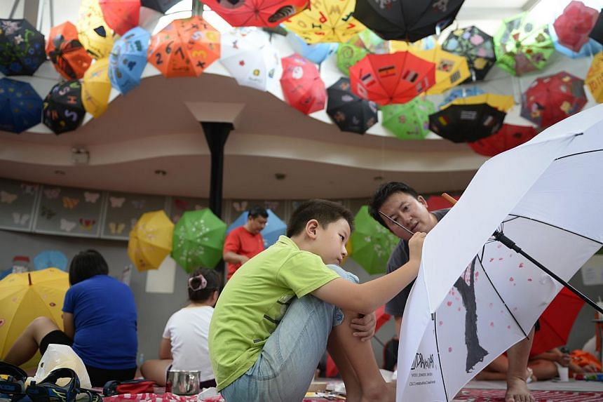 Father and son duo Wang Xiang Ru (left), nine, and Wang Jun, 44 decorate their umbrella with paintings during the umbrella painting competition held at Rain or Shine! at Marina Parade Community Centre on June 22, 2014. -- ST PHOTO: MARK CHEON
