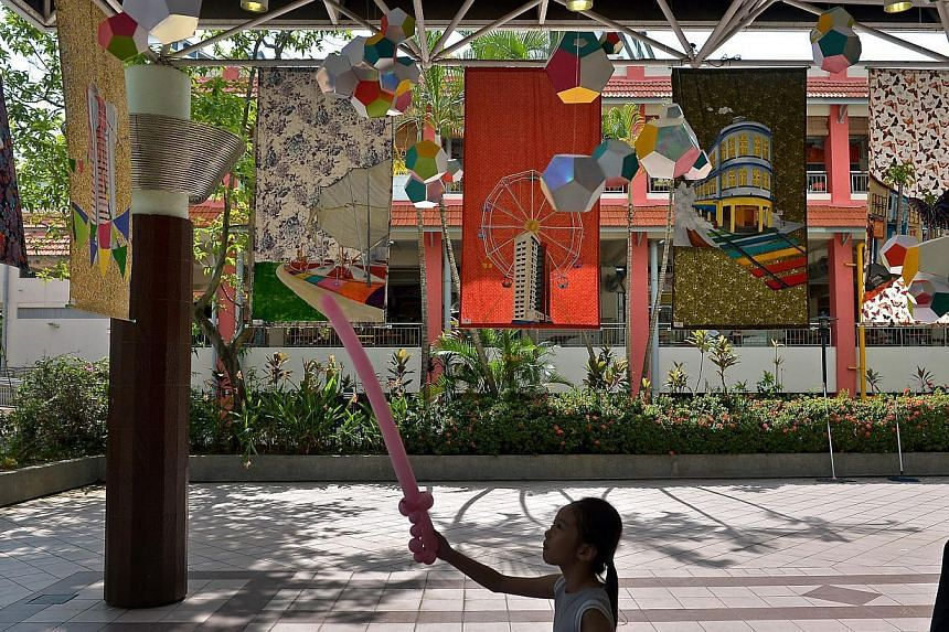 Peen Jin Xuan (centre), 6 , playing at the Colours of Carnival Installation which hang above him. -- ST PHOTO: KUA CHEE SIONG
