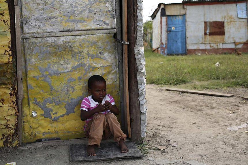 A child sits outside a locked shack in Nkaneng township, Marikana's informal settlement, in Rustenburg. -- PHOTO: REUTERS