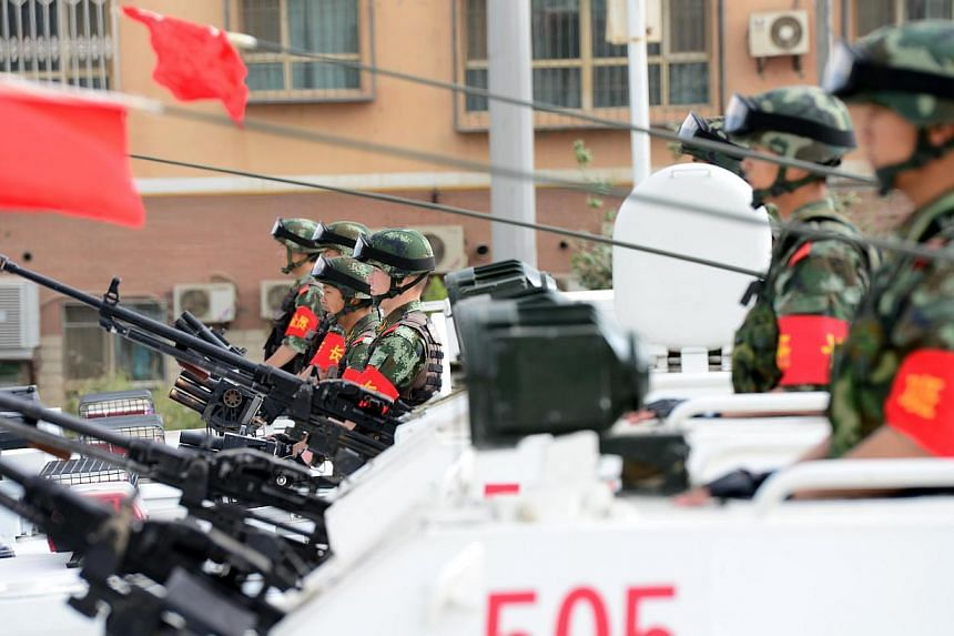 Security forces participating in a military drill in Hetian, northwest China's Xinjiang region on June 6, 2014. -- PHOTO: AFP